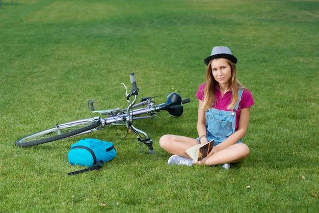 本を保持している草の上のbycicleの近くに座っている若い女の子