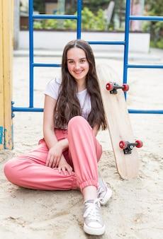 外のスケートボードの隣に座っている若い女の子