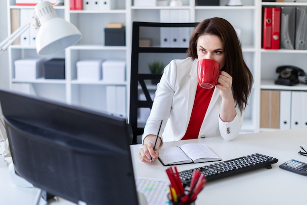 A young girl sitting in the office at the computer desk and holding a red cup.