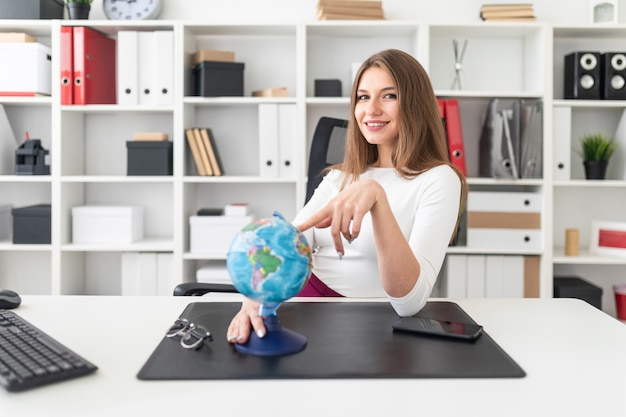 A young girl sitting in the office and in front of her on the table is a globe.