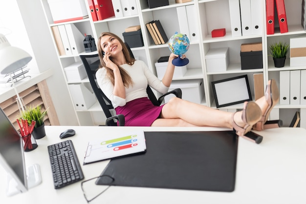A young girl sitting in the office, threw her legs on the table and holding a phone and a globe.