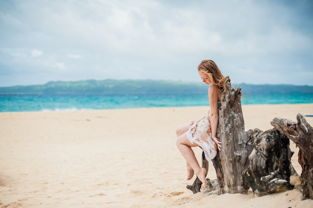 Young girl sitting on an old tree on the beach of boracay