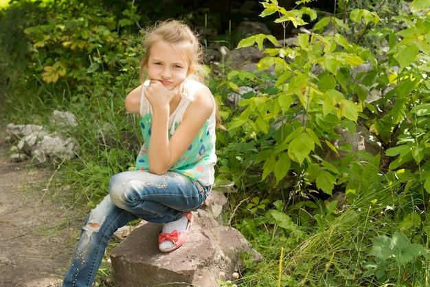 思考の岩の上に座っている少女