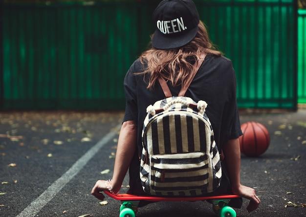 Молодая девушка сидит на пластиковой оранжевой копеечке на асфальте в кепке