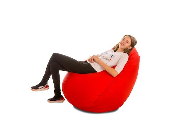 白で隔離赤いお手玉の椅子に座っている若い女の子