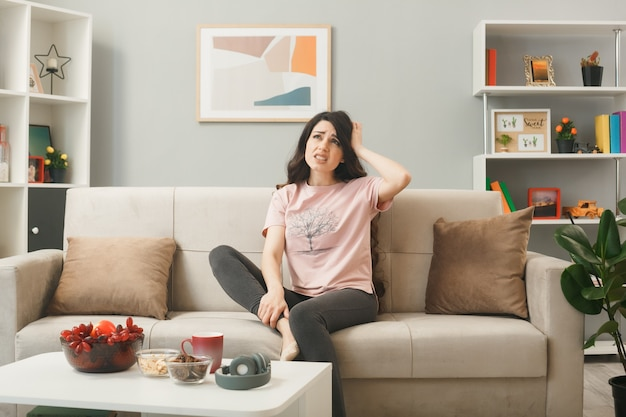 거실에 있는 커피 테이블 뒤에 소파에 앉아 있는 어린 소녀