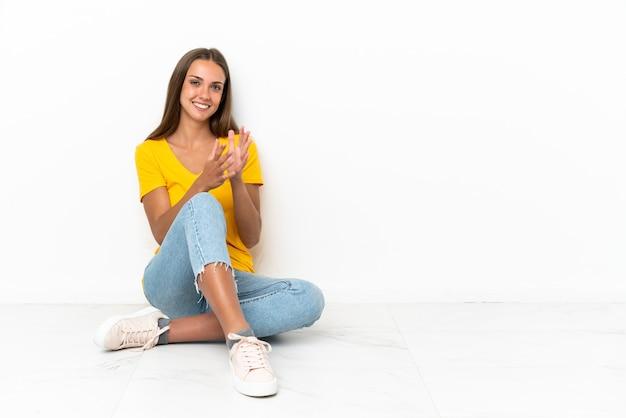 会議でのプレゼンテーションの後に拍手する床に座っている少女