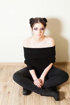 足を組んで床に座って、ナイトクラブに行く準備をしている若い女の子