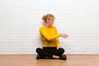 Молодая девушка сидит на полу после рукопожатия