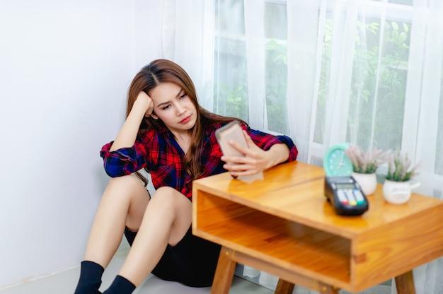 어린 소녀 그녀의 전화를보고 바닥에 앉아