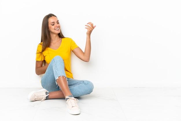 ギターのジェスチャーを作る床に座っている若い女の子