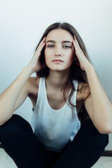 頭の上に手で床に座って若い女の子
