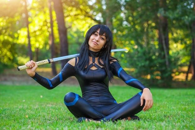 Молодая девушка сидит на траве и держит самурайский меч. оригинальный косплей персонажа