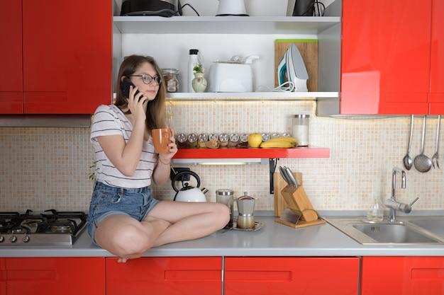 カップを置く電話で話している台所のテーブルに座っている若い女の子