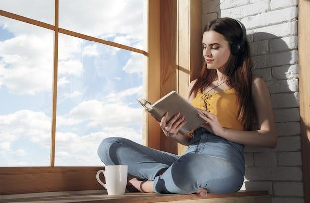 Молодая девушка сидит на подоконнике, слушая музыку