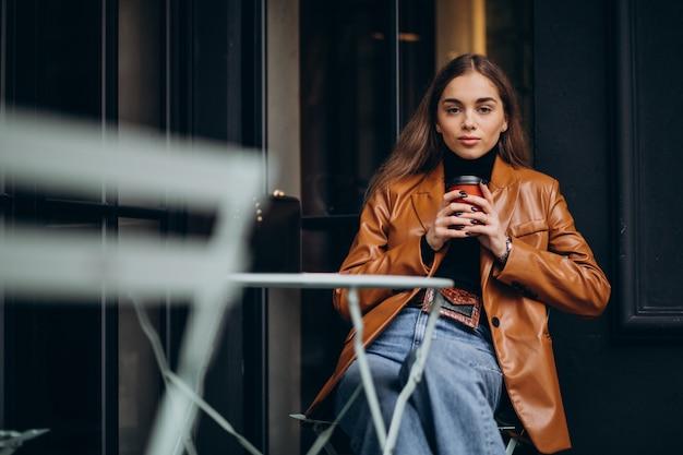 Giovane ragazza seduta fuori dal bar e bere caffè