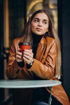Young girl sitting outside the cafe and drinking coffee