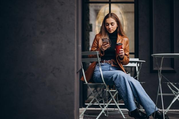 Молодая девушка сидит возле кафе и пьет кофе