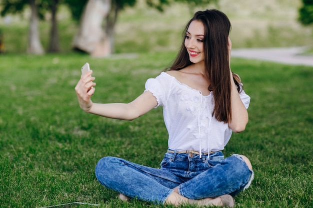 Young girl sitting in a park making an auto photo while smiling