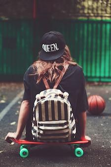 Young girl sitting on plastic orange penny shortboard on asphalt in cap
