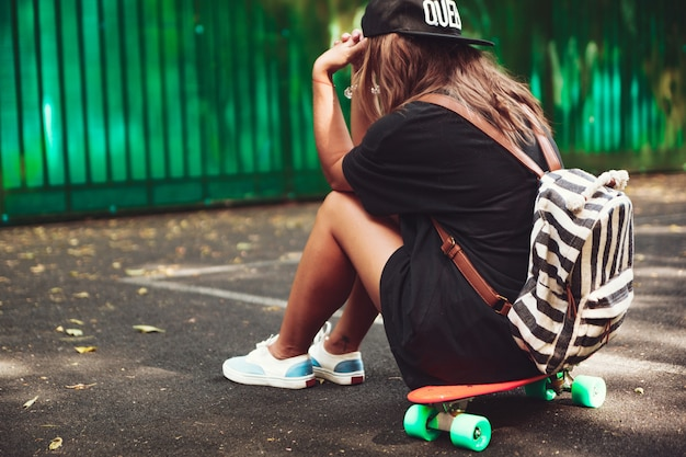 Young girl sitting on plastic orange penny shortboard on asphalt in cap