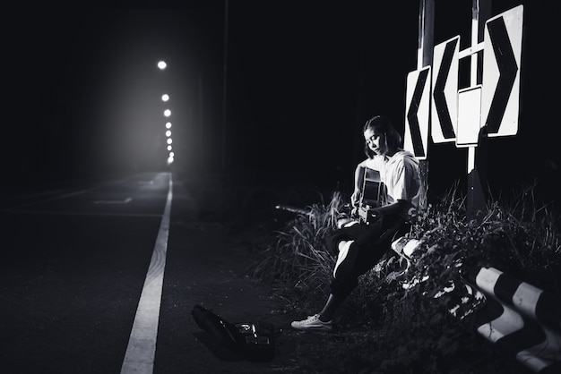 Young girl sitting and playing guitar on road side with road sign background, journey of musician concept
