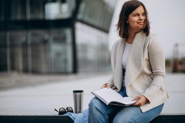 Молодая девушка сидит, читает книгу и пьет кофе на улице