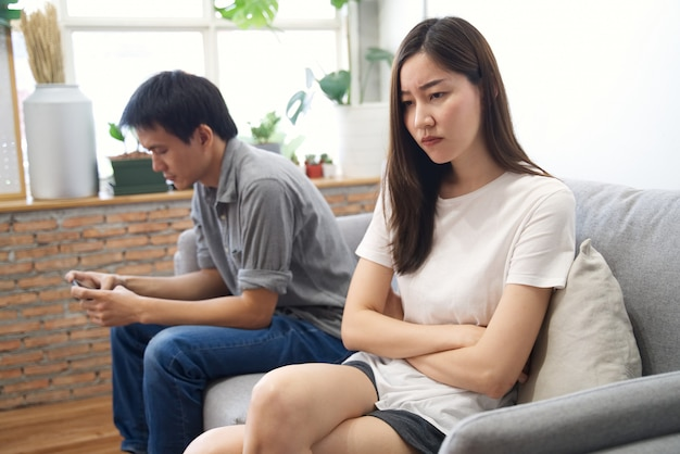 Young girl sitting on sofa is feeling bored with her boyfriend