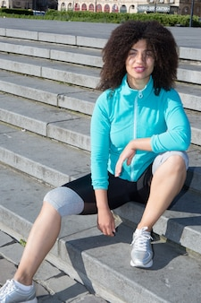 Young girl sitting on the street after jogging