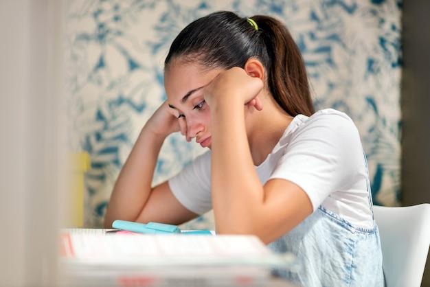 가까운 측면에서 교육 및 학습 개념으로 집에서 숙제를 공부하는 어린 소녀