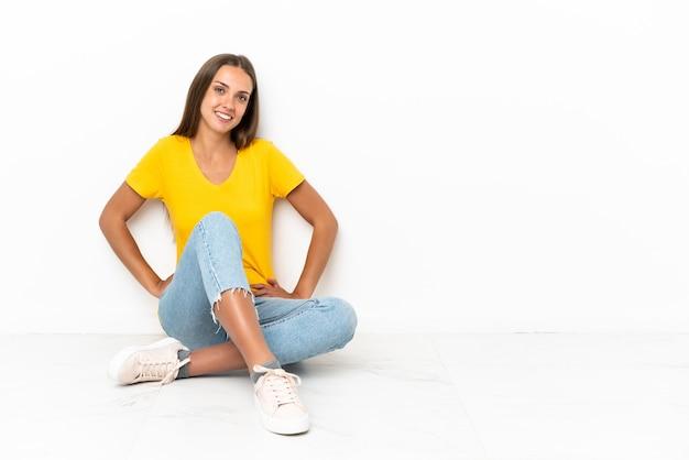 Молодая девушка сидит на полу, позирует с руками на бедрах и улыбается