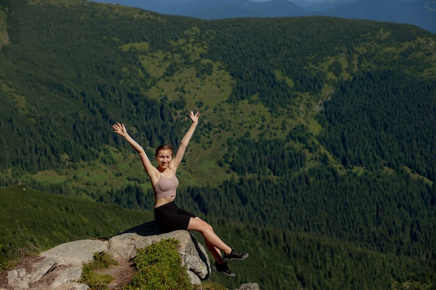 The young girl sitting at the top of the mountain raised her hands up on forest background. the woman climbed to the top and enjoyed her success.