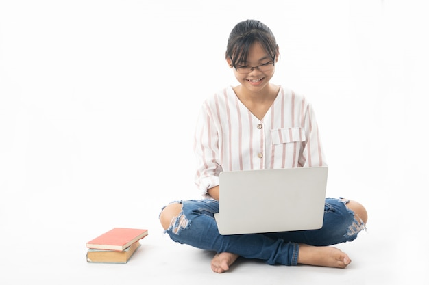 Young girl sitting and using laptop isolated on white