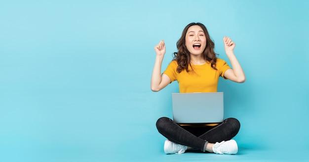ターコイズブルーの表情とジェスチャーでラップトップを使用して座っている若い女の子