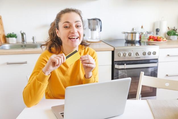 인터넷에서 구매하는 노트북과 함께 앉아있는 어린 소녀는 실내 부엌에 신용 카드 정보를 입력합니다.