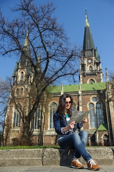 Young girl sitting with a map in hand. on background old church