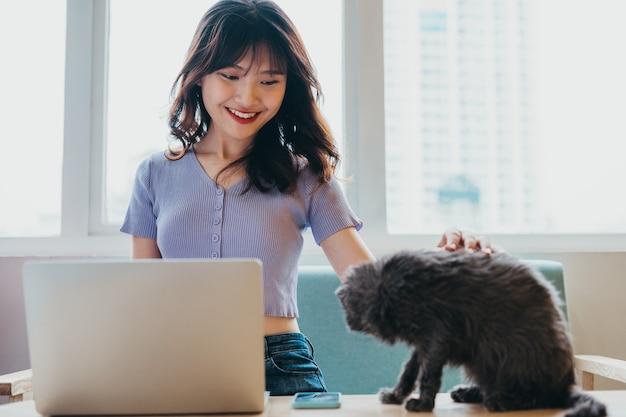 ソファに座って座っている少女とラップトップの隣に座っている猫