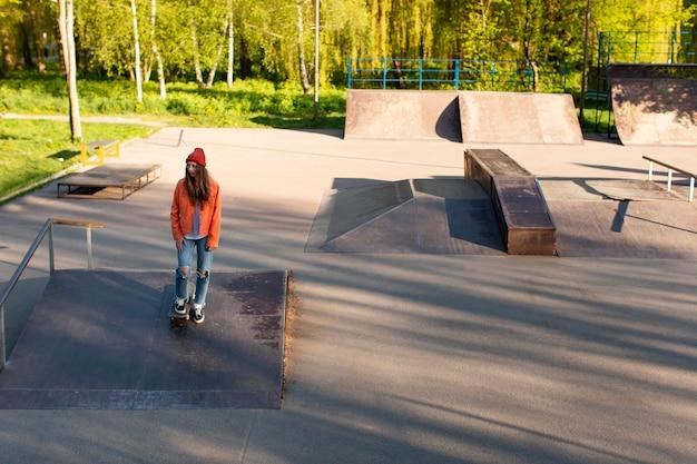 Young girl skating on ramp full shot