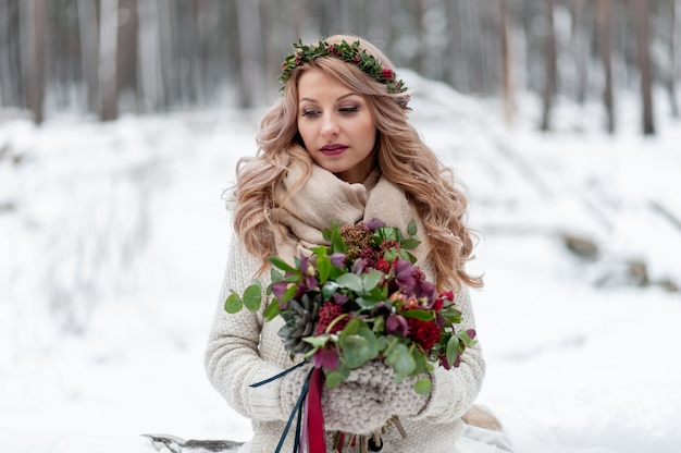 A young girl of slavic appearance with a wreath of wildflowers. beautiful blonde bride holds a bouquet in winter background.