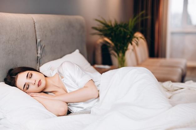 ベッドで寝ている少女。女性モデルと一緒にベッドで朝または夕方。寝室のベッドで目を閉じてシルクのパジャマを着たブルネット。