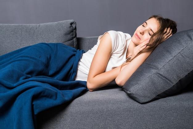 灰色の背景に青い掛け布団で覆われたソファで寝ている若い女の子