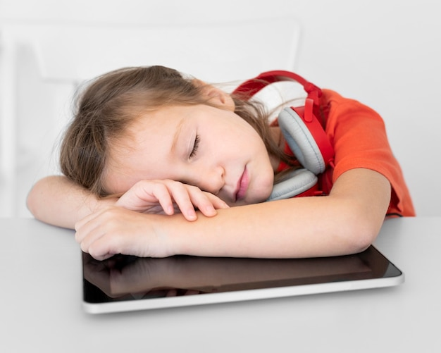 Young girl sleeping on tablet while wearing headphones