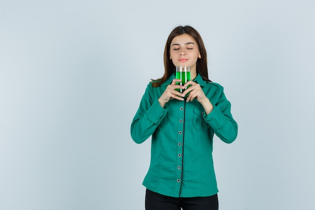 Young girl smelling glass of green liquid in green blouse, black pants and looking focused. front view.