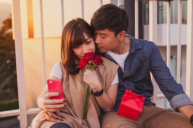 Young girl smelling some roses while her boyfriend takes a picture