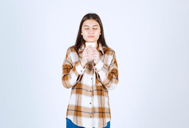 Молодая девушка пахнет ароматом чая на белой стене.