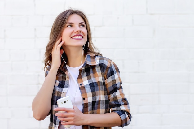 Young girl smiles and listens to music on the phone on a background of a white brick wall