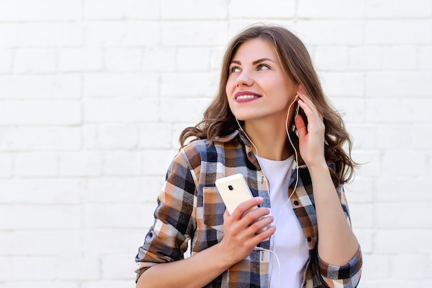 Young girl smiles and listens to music on the phone