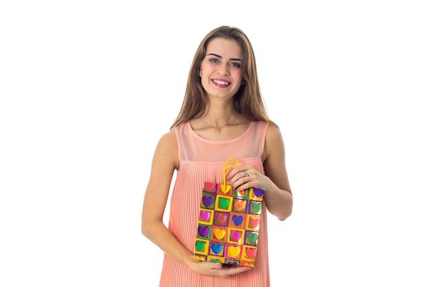 Молодая девушка улыбается и держит пакет крупным планом
