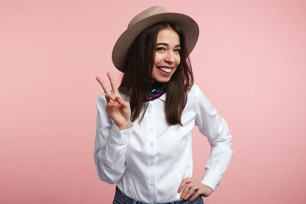 Молодая девушка улыбается и показывает жест мира над розовой студией