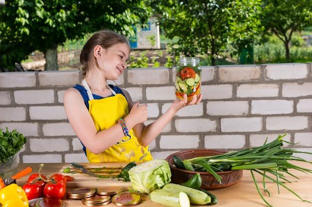 彼女は新鮮な野菜を積んだテーブルに立っている彼女はちょうど瓶詰めを終えたばかりの彼女の新鮮な野菜の瓶に微笑んでいる若い女の子